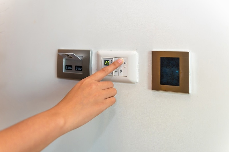 person changing the temperature on a thermostat