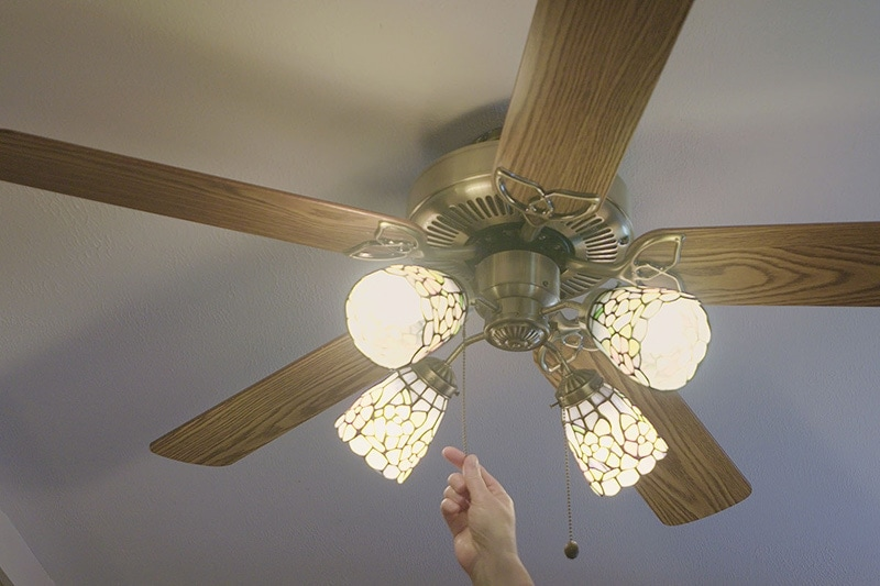 a person turning on their ceiling fan in order to save energy on their electrical bill